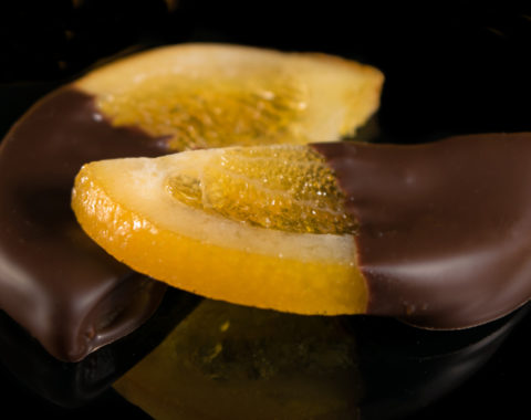 Orange slice dipped in half in dark couverture